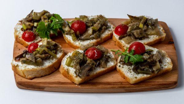 Bruskete classic sa francuskim hlebom, paprikom, cherry paradajzom i slaninom posluzeno na dasci