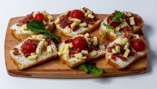 Bruskete sa prsutom francuski hleb, mozzarela i cherry paradajz posluzeno na dasci