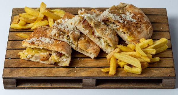 Italijanski sendvic sa piletinom uz dodatak parmezana i pomfrita posluzeno na dasci