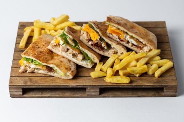 Club sendvic sa zenom salatom i jajima uz pomfrit posluzeno na dasci