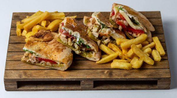 Pesto piletina sendvic sa dodatkom sosa u sendvicu i pomfrita posluzeno na dasci