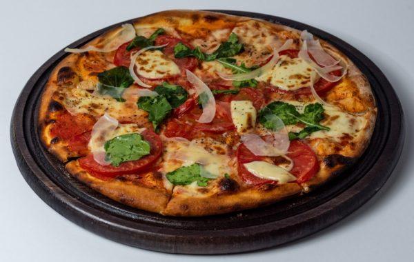 Pizza Capreze sa paradajzom, trapistom, kackavanjem sa dodacima povrca posluzeno na dasci